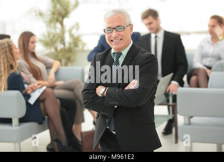smiling senior businessman on the background of business team - Stock Photo