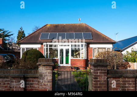 Solar panels on the roof of a small bungalow. - Stock Photo