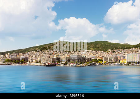 Sunlit Kavala cityscape, one of the biggest cities in northern Greece, blur motion sea water and white clouds above the mountain - Stock Photo