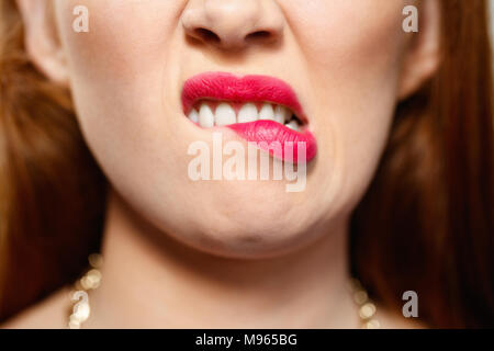 Portrait of insecure woman having doubts. Dubious redhead girl thinking, biting lips. Close up of mouth - Stock Photo