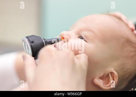 Infant in pediatric clinic. Close-up doctor's hand with modern otoscope examining baby's nose. Children healthcare and disease prevention. - Stock Photo