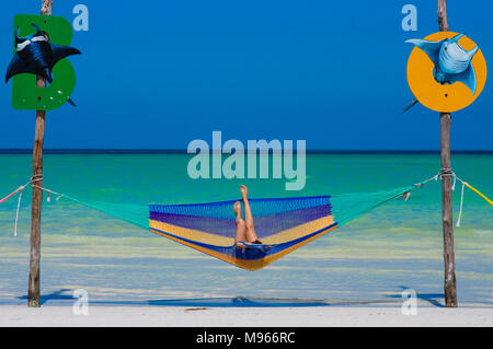 Woman relaxing in an hammock over a crystal clear water on the Caribbean sea with blue sky in Holbox, Mexico - Stock Photo