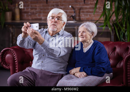 Senior couple taking selfie on smart phone while sitting on couch at home - Stock Photo