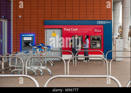 People withdrawing money from a Tesco ATM in Arena Retail Park, Coventry, West Midlands, UK. - Stock Photo