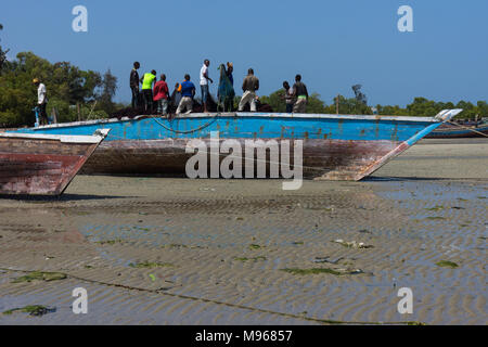 Fishermen working in a boat beached on the sand in Zanzibar - Stock Photo