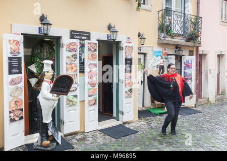 1 March 2018: Lisbon, Portugal - A young woman attracting business outside Restaurant Guerreiro in Lisbon Old Town. She is brandishing a piece of... - Stock Photo
