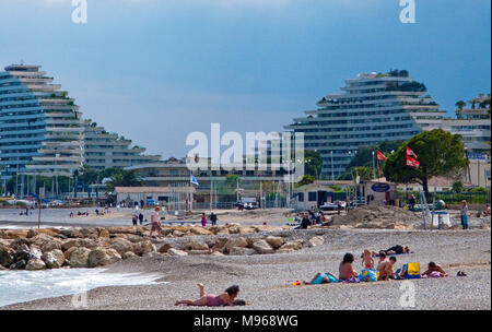 Evening mood at Pebble beach, Marina Baie des Anges, futuristic curved buildings at Villeneuve-Loubet-Plage, South France, Var, Cote Azur, France - Stock Photo