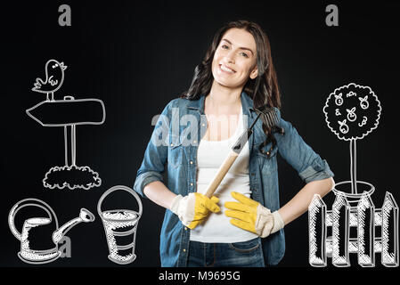 Cheerful young woman standing with a rake while working in the garden - Stock Photo