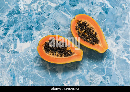 Two halves of papaya on a bright blue background. The view from the top - Stock Photo