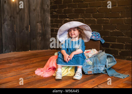 Little girl in white hat sitting in suitcase with things and look at the camera. Traveling with young children - Stock Photo