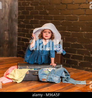 Little girl in a blue dress and white hat closes the suitcase with things. Little traveler preparing for a trip to Europe and Asia - Stock Photo