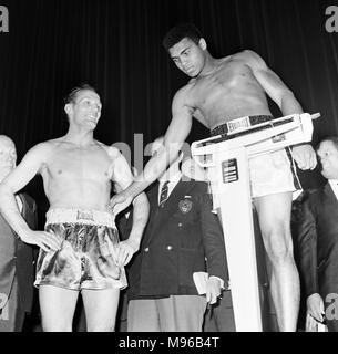 American world champion heavyweight boxer Muhammad Ali, formerly known as Cassius Clay, pictured at the Odeon Cinema in Leicester Square during the weigh in for his heavyweight title fight against British challenger Henry Cooper (left of Ali) at Highbury Stadium, North London.  Ali won the bout in the sixth round when the referee had to stop the fight due to a deep gash opening above Cooper's left eye. 23rd May 1966. - Stock Photo