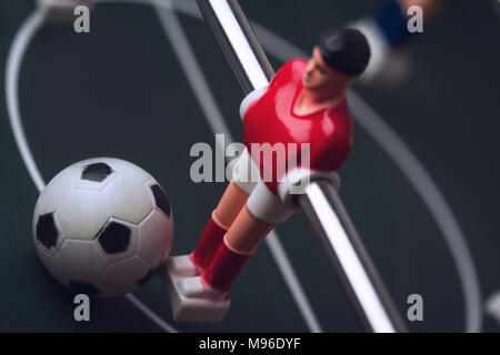 horizontal closeup with selective focus of red shirt player figurine with ball at his feet on foosball table soccer game - Stock Photo