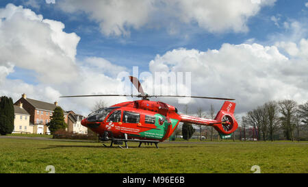 Wide angle view of an Airbus helicopter of the Wales Air Ambulance service on the ground in a housing estate on an emergency mission - Stock Photo