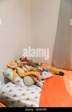 Girl hiding in bed behind stuffed animals - Stock Photo