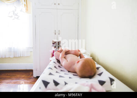 Baby laying on changing table with mask in background