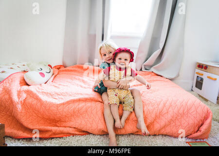 Girl holding baby on bed - Stock Photo