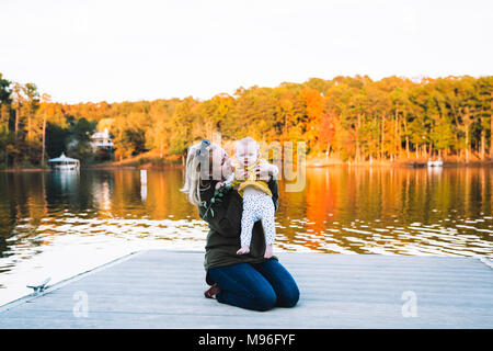 Woman holding baby on dockside - Stock Photo