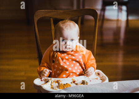 Baby making a mess eating in high chair