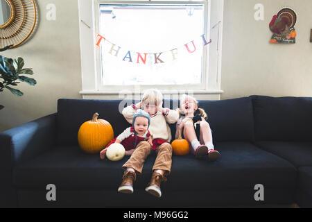 Children sitting underneath thankful banner with pumpkins - Stock Photo
