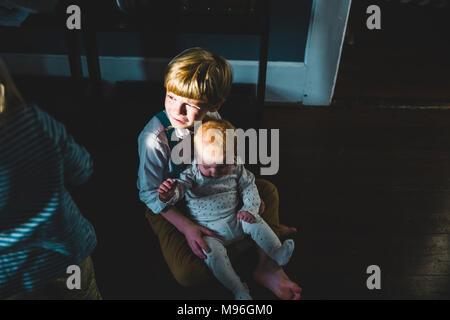 Baby sitting on boy's lap - Stock Photo