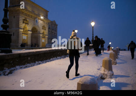motion shot of young woman with white winter bobble hat walking in snow in near Porte de Peyrou in central Montpellier, France - Stock Photo