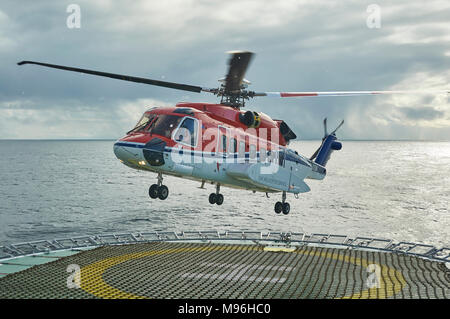 A S92 helicopter from CHC Helicopter Services landing on a Seismic Vessel during a Snow Flurry in the Norwegian North Sea. - Stock Photo