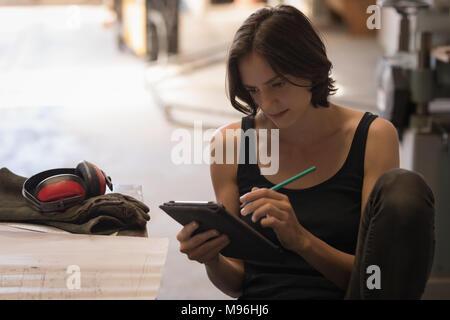 Female welder using digital tablet - Stock Photo