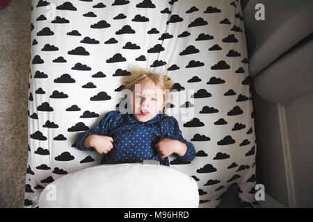 Girl laying on bed with cloud decal - Stock Photo