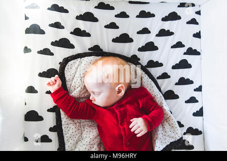 Baby sleeping on bed with cloud decal - Stock Photo