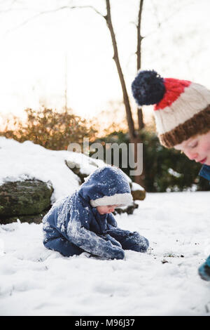 Two boys playing in the snow, making snowballs - Stock Photo