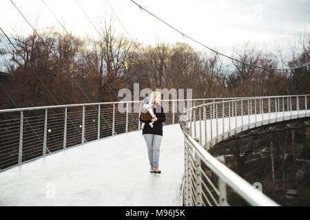 Woman holding child on a metal bridge - Stock Photo