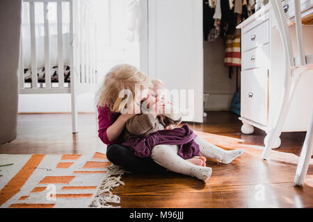 Girl with baby laying on her lap - Stock Photo