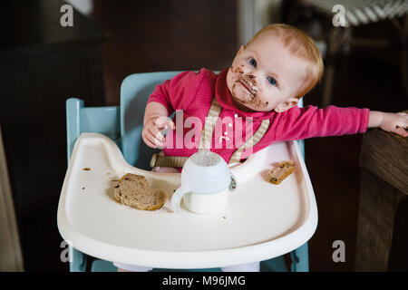 Baby in high chair with messy face eating meal - Stock Photo