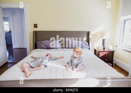 Girl and baby playing on bed - Stock Photo