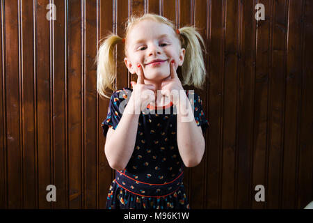 Girl with pigtails pulling faces - Stock Photo