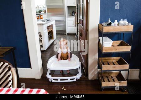 Baby in walker going through doorway - Stock Photo