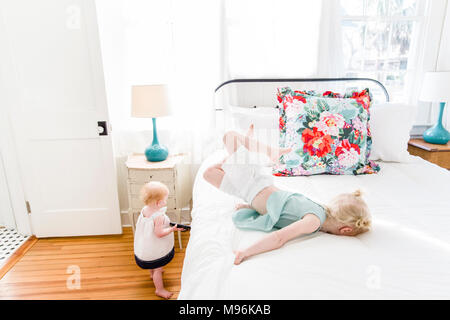 Girl laying on bed with baby next to her - Stock Photo