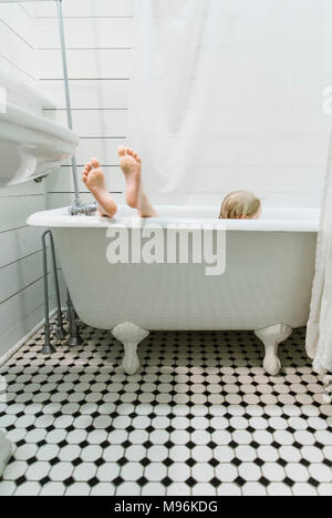 Brother and Sister playing in bathtub - Stock Photo