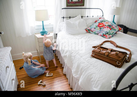 Girl and baby in bedroom - Stock Photo