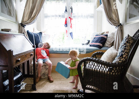 Boy and baby in nautical style bedroom - Stock Photo