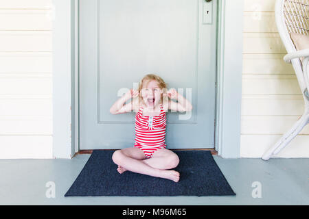 Girl pulling faces outside of door - Stock Photo