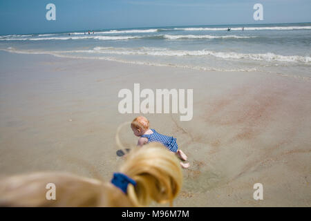 Baby sitting in water on beach - Stock Photo