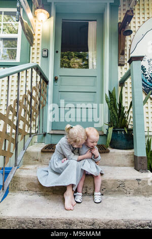 Girl and baby sitting outside on steps - Stock Photo