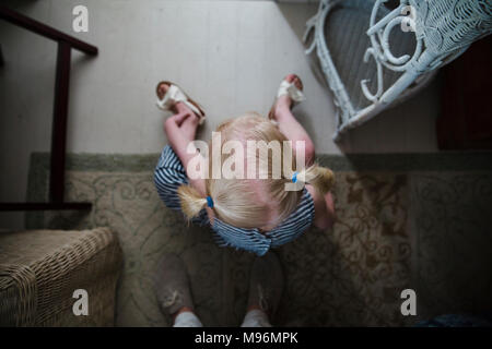 Girl with pigtails sitting in front of someone - Stock Photo