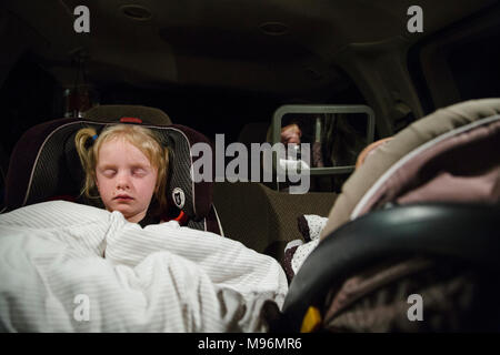 Two children sleeping in car seats - Stock Photo