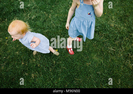 Baby and girl standing in field - Stock Photo