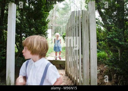 Two children wander around gate - Stock Photo