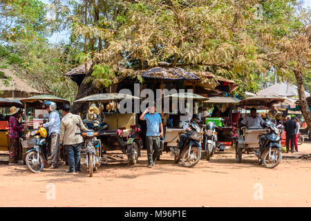 Drivers wait with their parked tuk-tuks (motorcycles with a trailer used as a taxi) in Cambodia. - Stock Photo