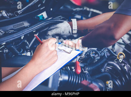 Asian women engineers and technicians are checking mechanic and inspecting on a car in auto repair shop the list on the board - Stock Photo